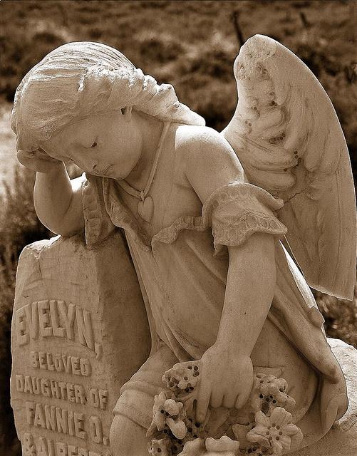 Скульптура в виде девочки-ангела на памятнике